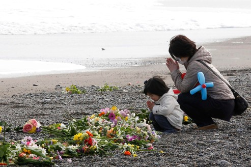 A mother and her daughter offer prayers for victims of the March 11, 2011 earthquake and tsunami disaster at a seaside which was damaged by the disaster in Iwaki, Fukushima prefecture, March 11, 2012, to mark the first anniversary of the earthquake and tsunami that killed thousands and set off a nuclear crisis. REUTERS/Kim Kyung-Hoon (JAPAN - Tags: ANNIVERSARY DISASTER)