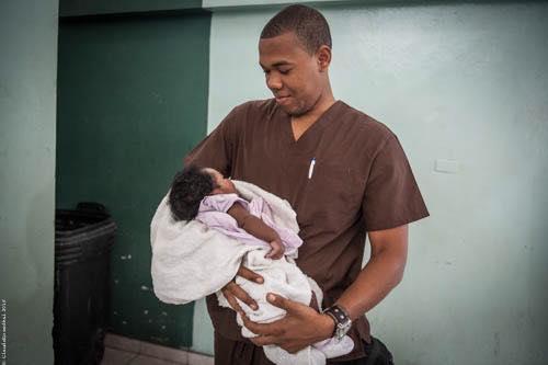 Un obstétricien haitien, formé par GSF, porte un bébé qu'il vient de mettre au monde, en Haiti.