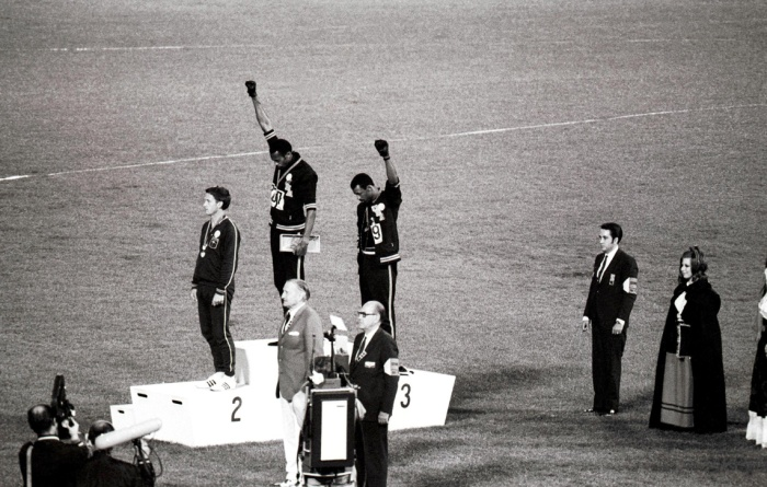 """Jeux olympiques de Mexico. Podium du 200 mètres masculin, de g. à dr. : Peter Norman (Australie, 2ème), Tommie Smith et John Carlos (Etats-Unis, respectivement 1er et 3ème, faisant le signe du """"Black Power""""), 16 octobre 1968."""